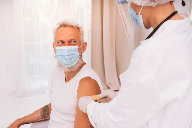 O médico aplica um adesivo no paciente após a vacina invejável