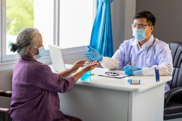 O médico asiático aconselhou a idosa a lavar as mãos com álcool antes do tratamento para evitar a infecção inicial pelo vírus corona.