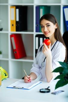 O médico assina um plano de dieta. o nutricionista detém os punhados de tomate fresco. frutas e vegetais.
