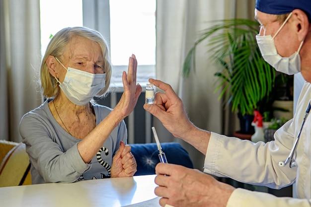 O médico atencioso ajuda uma avó idosa negativa de 85 anos - um paciente em casa ou no hospital.