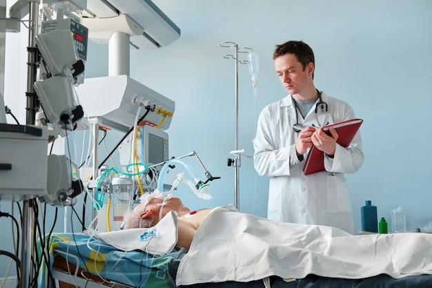 O médico caucasiano de cuidados intensivos examina a postura crítica intubada do paciente, escrevendo notas para relato de caso no departamento de terapia intensiva