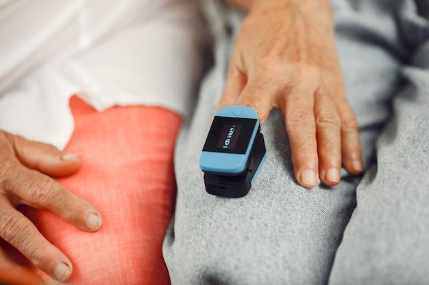 O médico coloca um monitor de frequência cardíaca no dedo do paciente. o homem segura a mão de uma mulher.