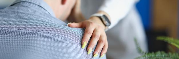 O médico colocou a mão com simpatia no ombro de um paciente do sexo masculino chateado