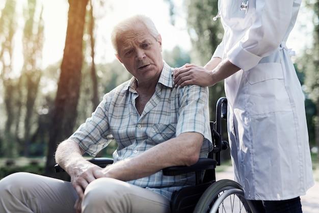 O médico colocou a mão no ombro do velho triste