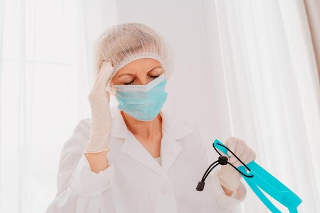 O médico com máscara e protetor facial está cansado da terrível pandemia do vírus