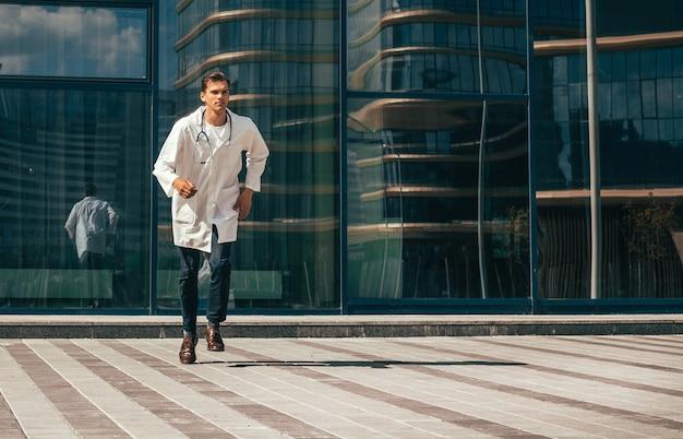 O médico com um estetoscópio corre rapidamente ao longo de uma rua da cidade. foto com uma cópia-espaço.