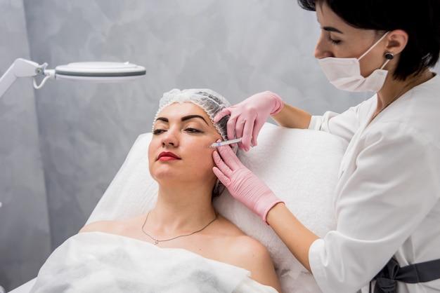 O médico cosmetologista faz o procedimento de injeções faciais. jovem mulher em um salão de beleza.