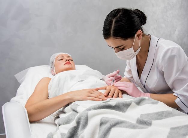O médico cosmetologista faz o procedimento de injeções nos braços. jovem mulher em um salão de beleza.