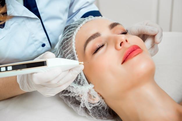 O médico cosmetologista faz o procedimento de rejuvenescimento das injeções faciais para apertar e suavizar as rugas na pele do rosto de uma mulher jovem e bonita em um salão de beleza