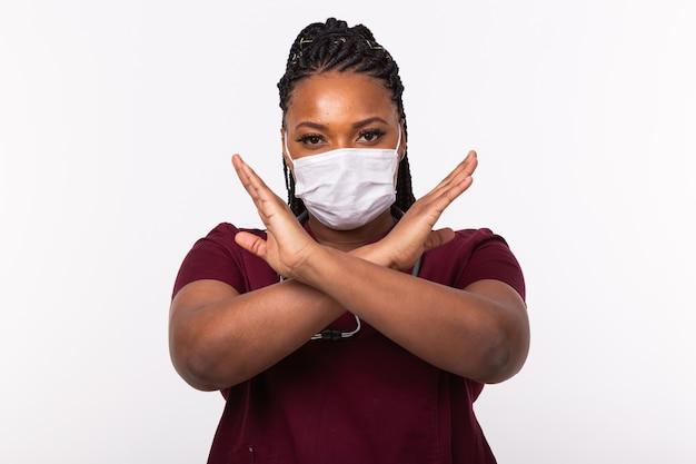 O médico cruzou as mãos no peito na parede branca. ele está usando máscara médica. não ou pare o gesto