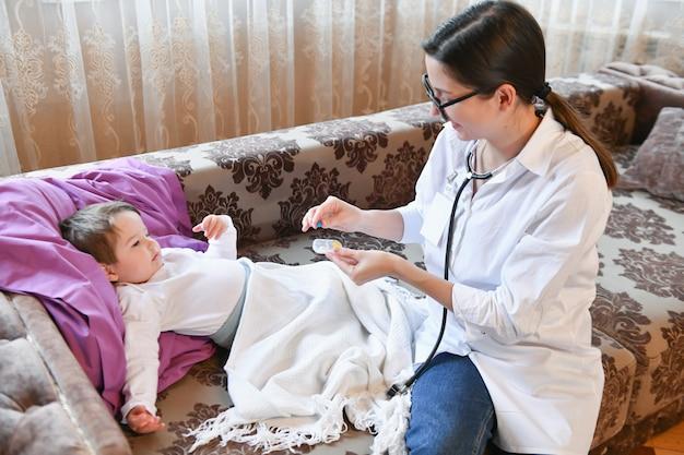 O médico dá a pílula para a criança. médica em casa. o pediatra fornece vitaminas a um paciente pequeno após o exame.