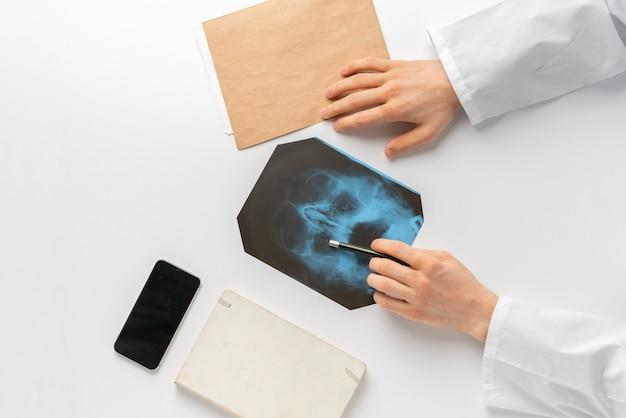 O médico dá as mãos ao longo do raio x do corpo humano e examina os ossos