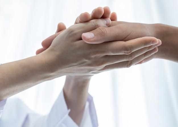 O médico de mãos dadas, segurando a mão do paciente para encorajamento e explicou os resultados do exame de saúde.