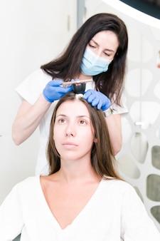 O médico dermatologista examina o cabelo e o couro cabeludo das mulheres com aparato especial para diagnóstico