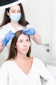 O médico dermatologista examinando o cabelo e o couro cabeludo de mulheres