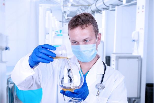 O médico derrama o líquido em um copo com conhaque.