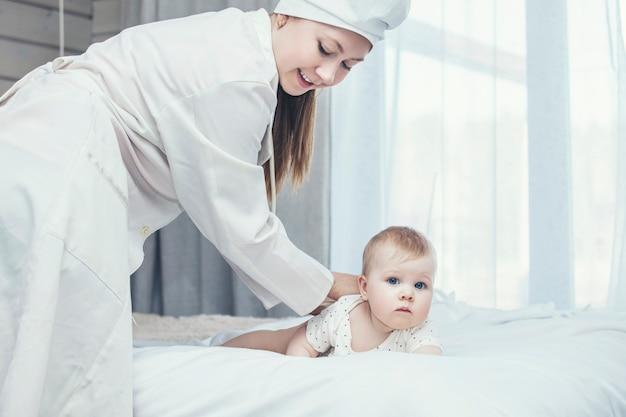 O médico desafia e trata uma criança pequena em uma sala branca