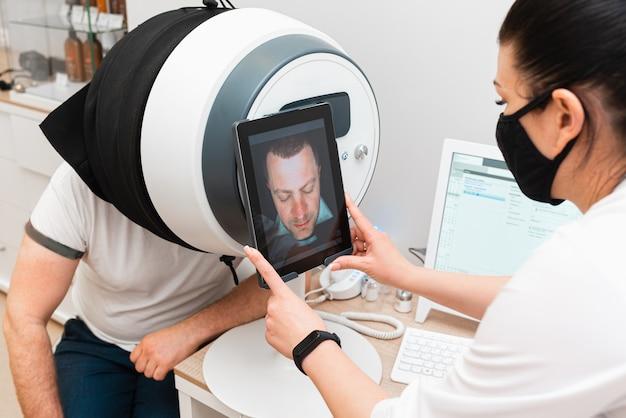 O médico diagnostica a condição da pele do rosto do homem usando modernos equipamentos cosméticos.