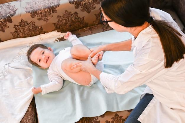 O médico em casa faz ginástica para a criança