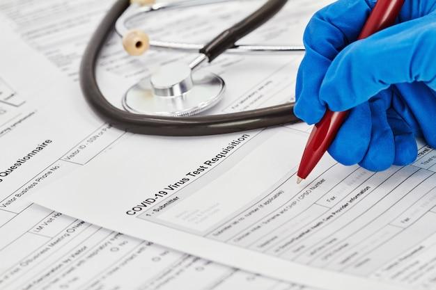O médico em luvas médicas azuis está se preparando para preencher um formulário de requisição de teste de vírus. estetoscópio no fundo. fechar-se.