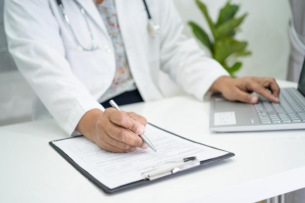 O médico escreve a nota médica na área de transferência com o laptop no hospital.