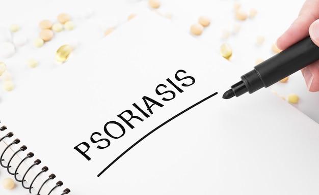 O médico escreve a palavra psoríase em um bloco de notas branco