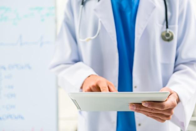 O médico está de pé e olhando para o tablet.
