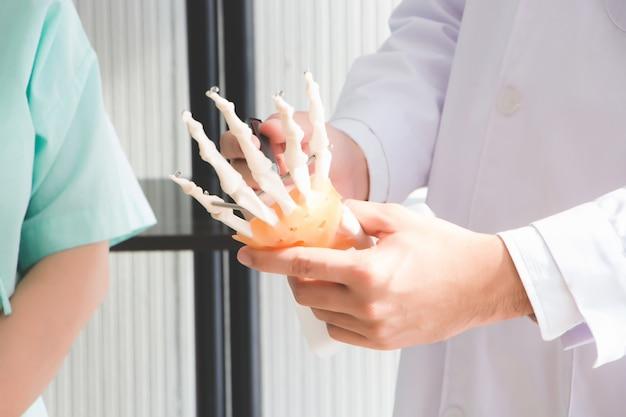 O médico está explicando a causa da dor nas mãos devido ao uso prolongado de mãos tensas.