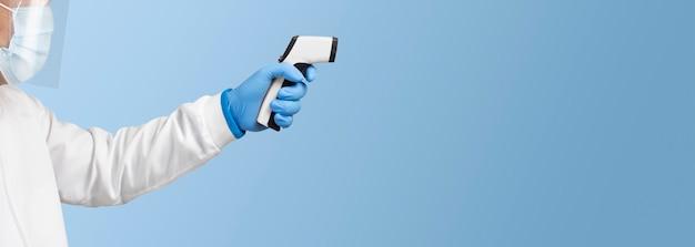 O médico está medindo a temperatura com um termômetro infravermelho branco em uma cor azul