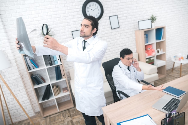 O médico está olhando para o raio-x no consultório médico.