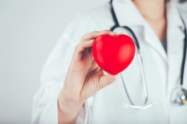 O médico está segurando e mostrando um coração vermelho.