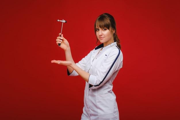 O médico está segurando um martelo neurológico em um fundo vermelho. o neurologista verifica os reflexos do paciente com um martelo. diagnósticos, cuidados de saúde e cuidados médicos.