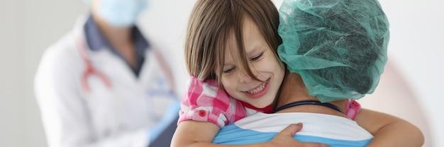 O médico está segurando uma menina nos braços