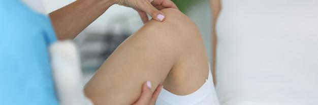 O médico examina a perna de uma mulher após um ferimento no consultório