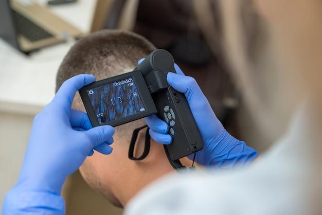 O médico examina o couro cabeludo do paciente usando um dispositivo óptico