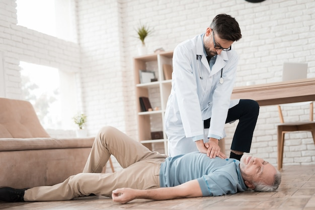 O médico faz cpr para o homem idoso que tem ataque cardíaco.