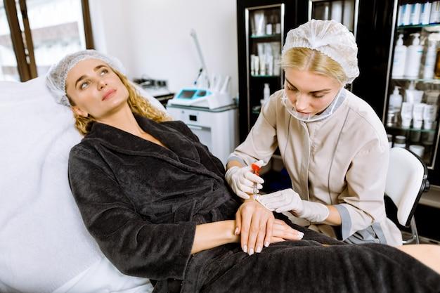 O médico faz injeções de toxina botulínica nas mãos de uma mulher contra a hiperidrose e na pele contra as rugas.