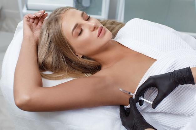 O médico faz injeções intramusculares de toxina botulínica na região das axilas contra a hiperidrose.
