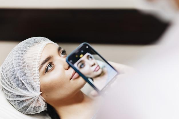 O médico faz uma foto dos lábios antes do realce para ver a diferença. a jovem garota com um rosto bonito em um rosto especial.