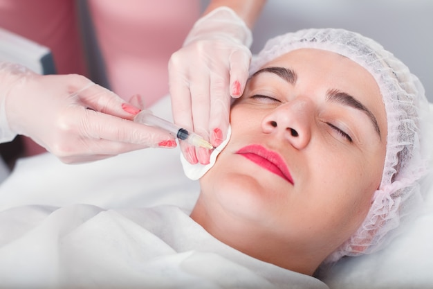 O médico faz uma seringa de injeção no rosto da mulher. tratamento de regeneração.