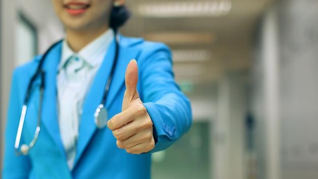 O médico feminino mostrando o gesto bem no fundo do borrão