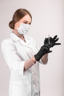 O médico mascarado de jaleco branco segura uma seringa na mão