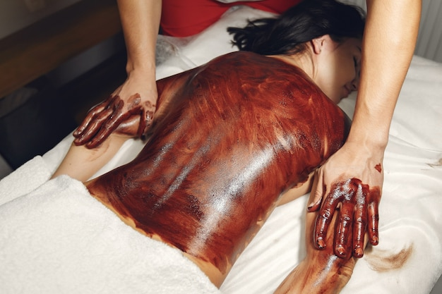 O médico massageia a mulher com um chocolate