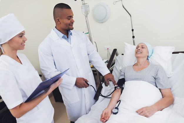 O médico mede a pressão sobre a mulher.