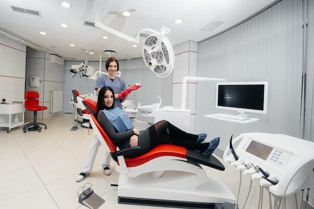 O médico mostra um molde da mandíbula do paciente. odontologia