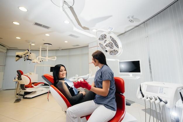 O médico mostra um molde da mandíbula do paciente