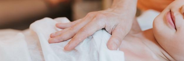 O médico osteopata mãos faz terapia fisiológica e emocional para uma menina de oito anos. sessão de tratamento de osteopatia pediátrica. medicina alternativa. cuidar da saúde da criança. bandeira
