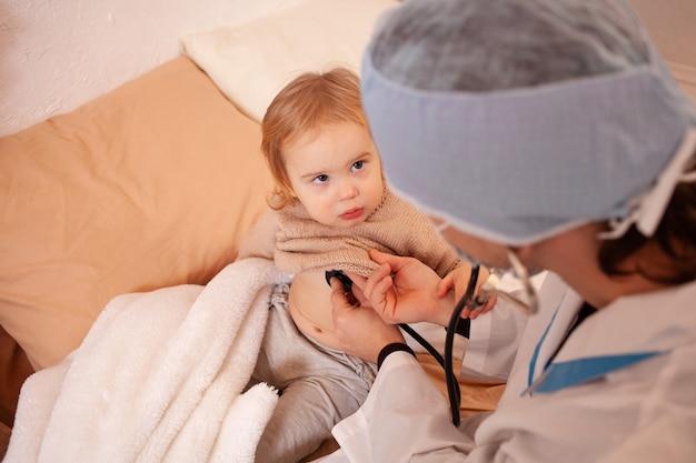 O médico ouve o coração e os pulmões de uma menina em casa. bebê doente, quarentena domiciliar, coronavírus, cobiça.