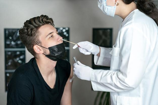 O médico pega um cotonete do nariz do jovem homem teste de dna teste de pcr coleta de cotonete de coronavirus