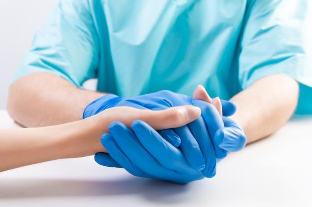 O médico pegou cuidadosamente a mão do paciente